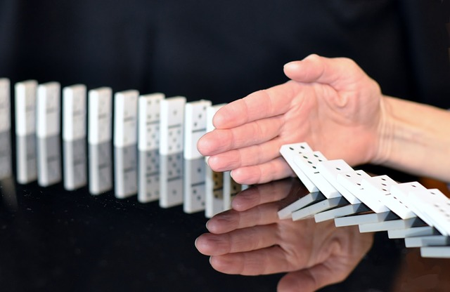 Hand Stopping Falling Dominos Image
