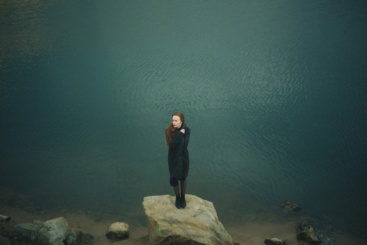 woman standing at a lake links to article