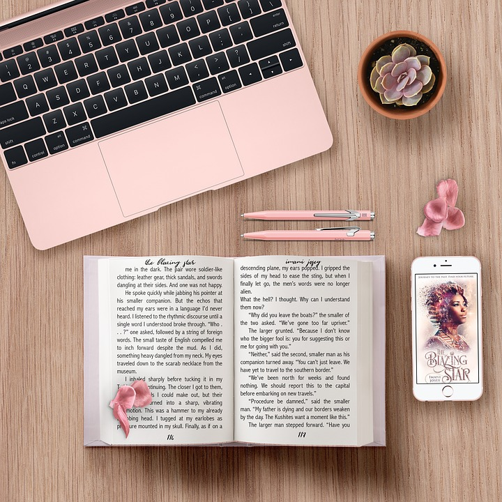 Desktop with laptop, book, pens, and smartphone Image