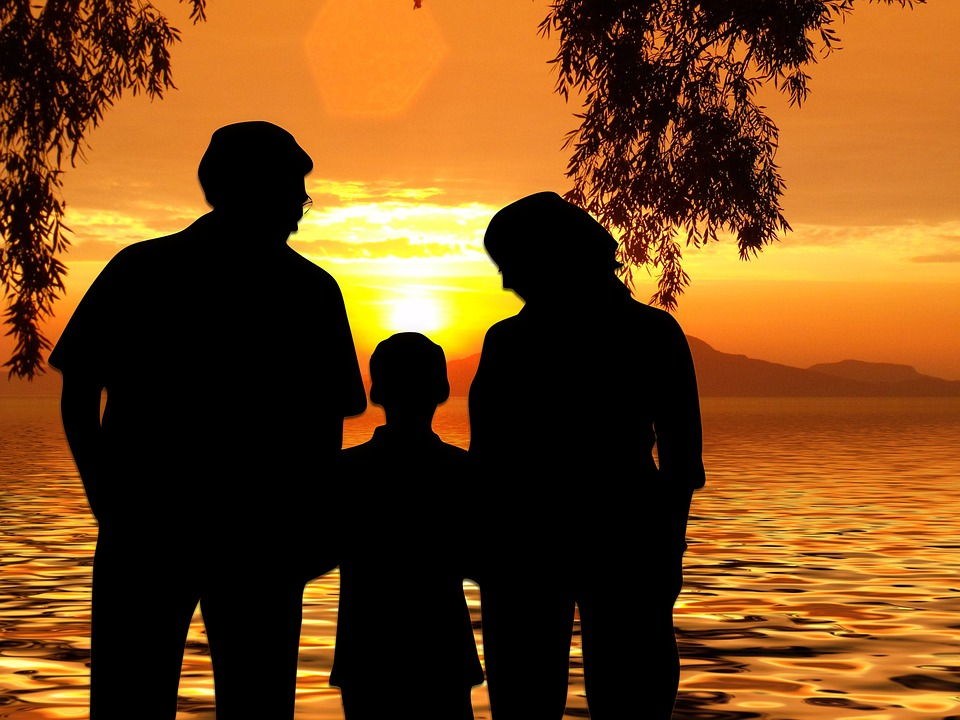 Family looking at sunset across a lake image