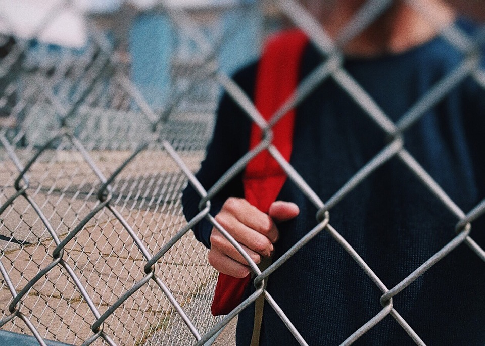 teenager behind a fence image