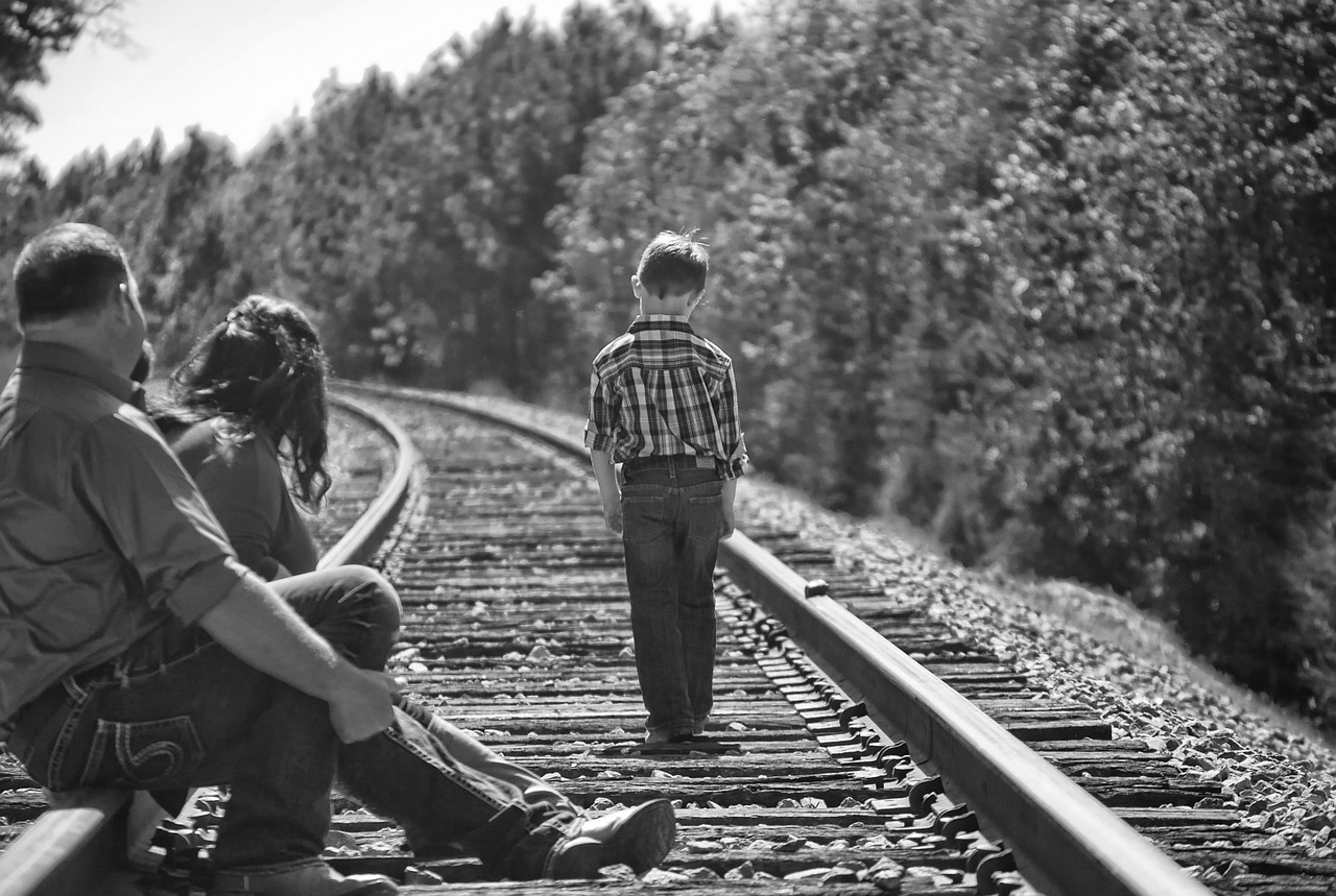 boy and parents walking on train tracks image
