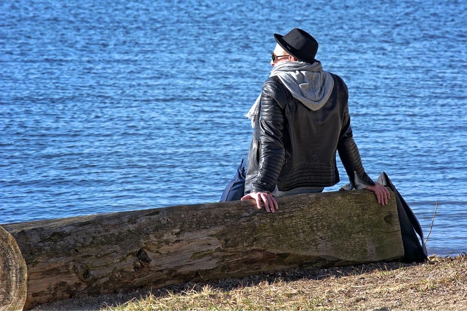 man sitting alone on log image