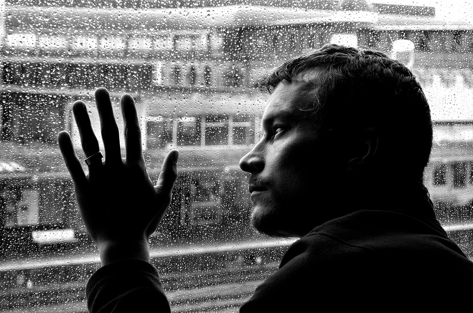 lonely man looking out window image