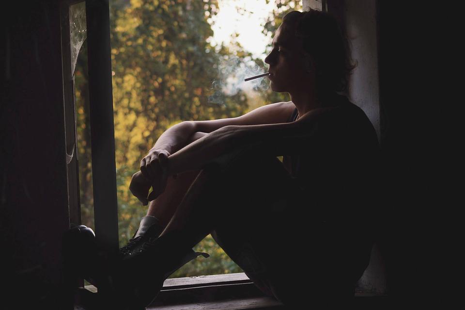 Man Sitting in Windowsill Smoking Image