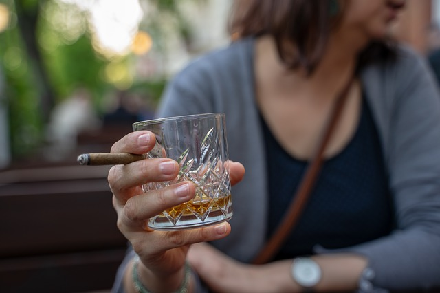 Woman Holding Whiskey Glass and Cigar Image