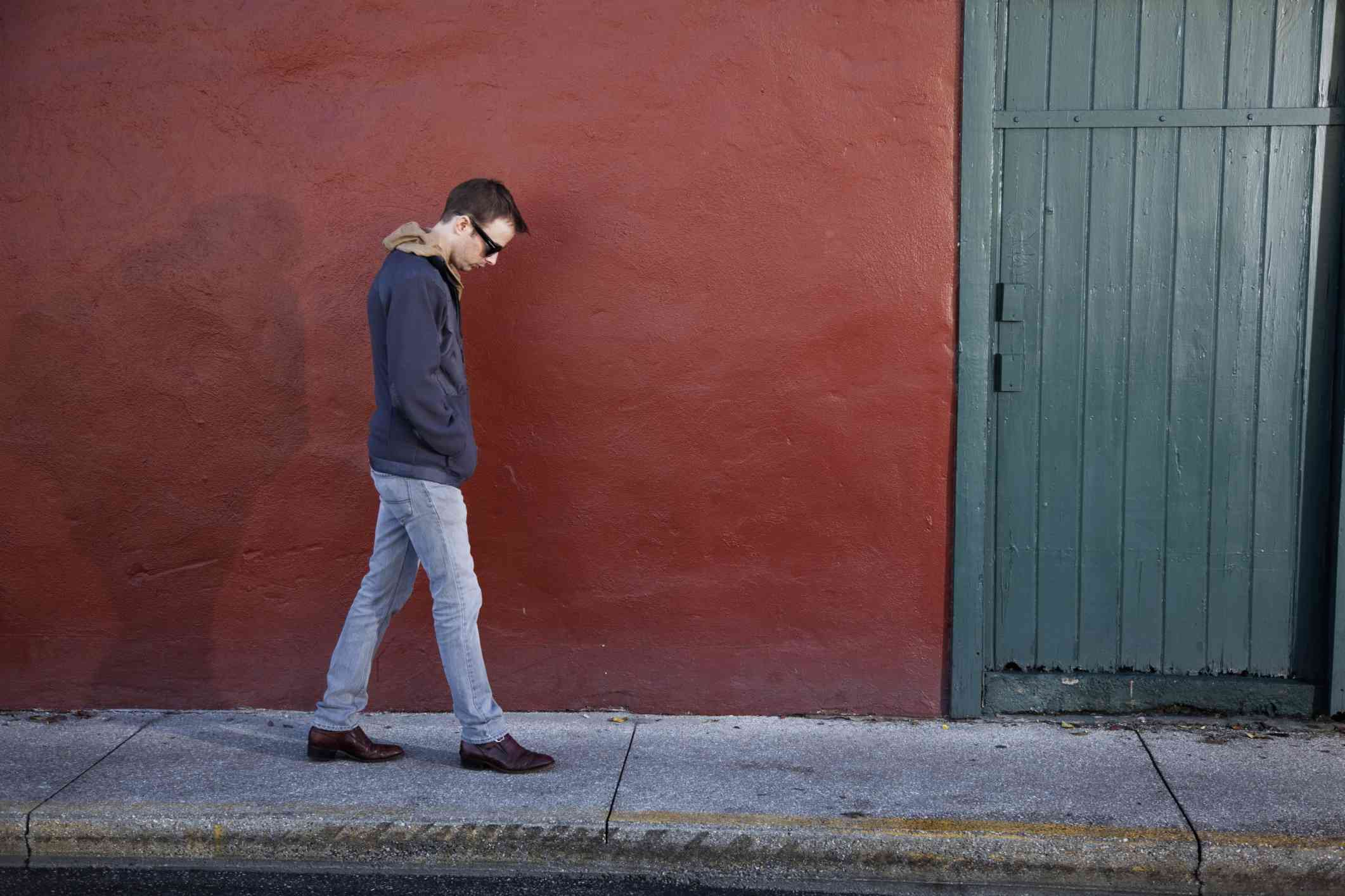 Man walking down a sidewalk image