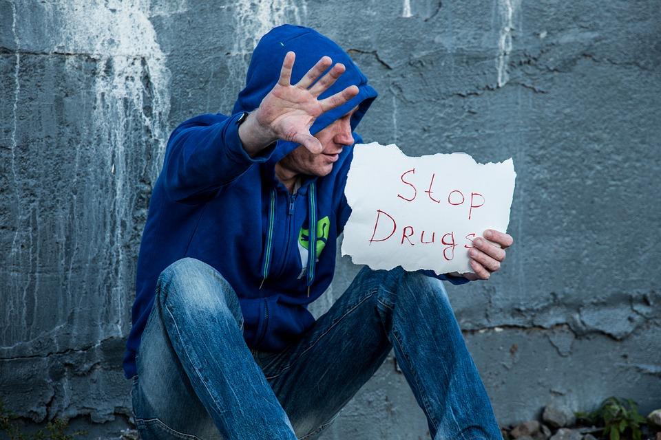 "Man Holding Sign Saying ""Stop Drugs"" Image"