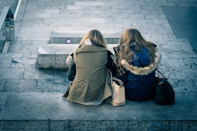 two women sitting on a bench
