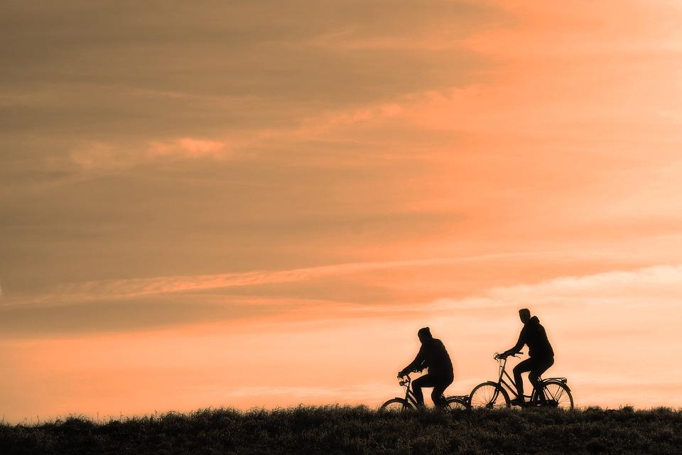 people riding bikes at sunset image